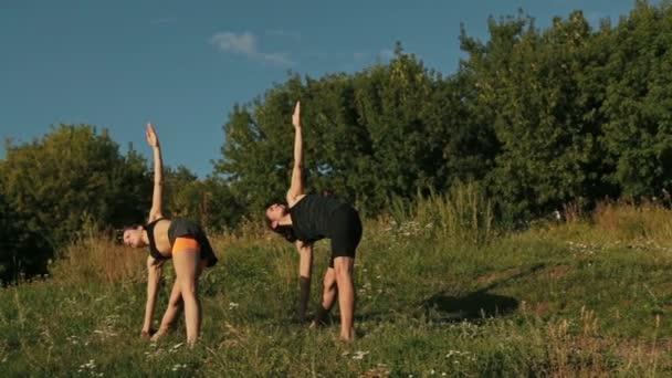 Sportovní muž a žena, která dělá trojúhelník představují v parku při západu slunce
