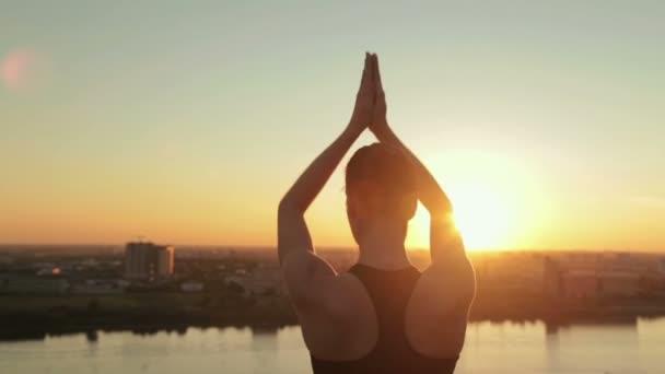 Sportovní žena cvičí jógu v parku při západu slunce - pozdrav slunci