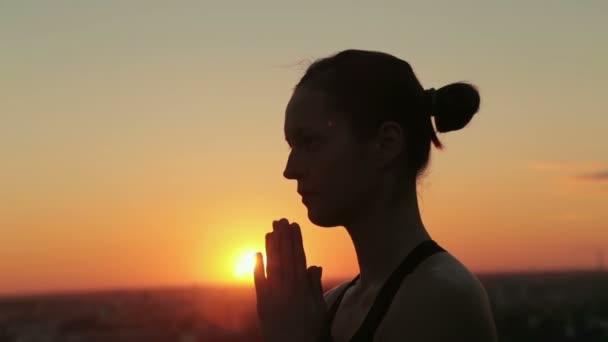 Sportovní žena cvičí jógu v parku při západu slunce, takže ruku s pozdravem namaste