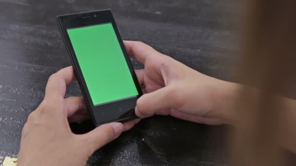 Žena dívá na smartphone se zelenou obrazovkou