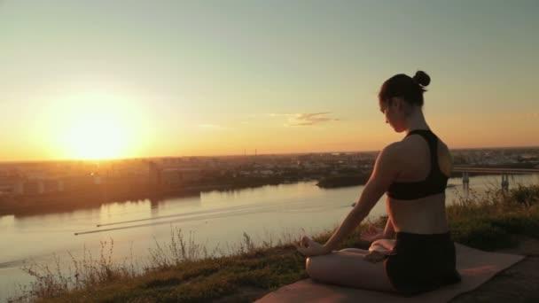 Sportovní žena v lotosové pozici v parku při západu slunce