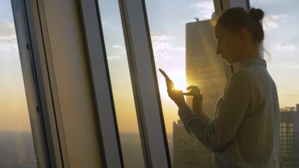 Zpomalený pohyb: žena pomocí smartphonu proti západu slunce pohled na město přes okno