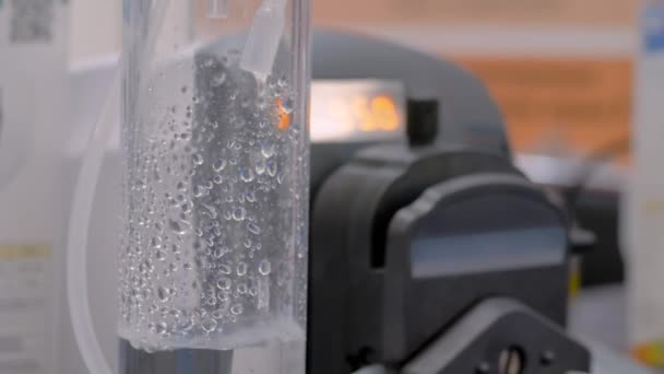 Slow motion: droplets falling from tube - compact liquid dosing system: close up
