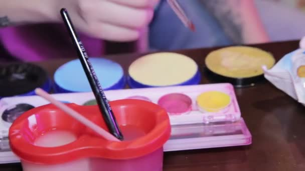 Woman draws with watercolors at the table
