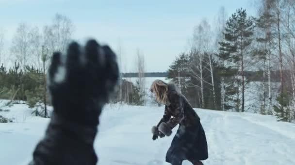 Pár s sněhová koule bojovat ve sněhu v zimním lese, slowmotion