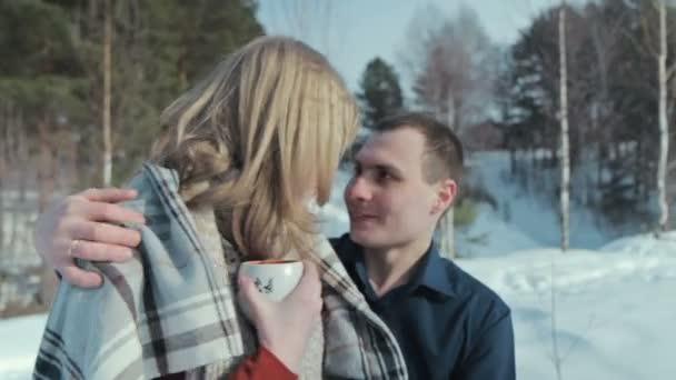 Junges Paar verliebt in einen Winterurlaub genießen die Natur und trinken heißen Tee
