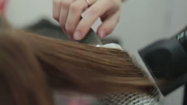 Kadeřník s kartáčem a fénem. Kadeřník sušení vlasy ženy klienta. žena v Kadeřnictví Kosmetika