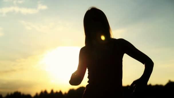 Sziluettjét a tánc gyönyörű naplemente alatt nő. Természetes fény és a sötétség.