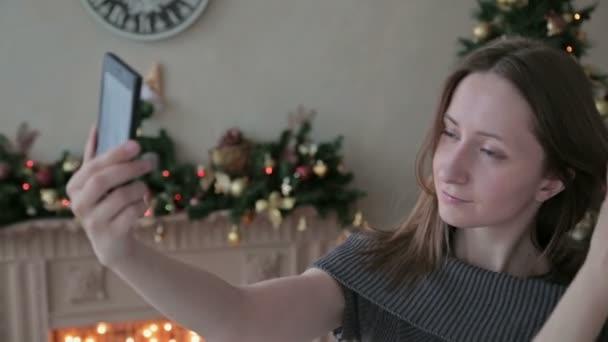 Junge hübsche Frau nehmen Selfie zu Hause sitzen in der Nähe von Weihnachtsbaum