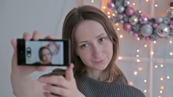 junge hübsche Frau macht Selfie zu Hause, während sie in der Nähe der Weihnachtsdekoration sitzt