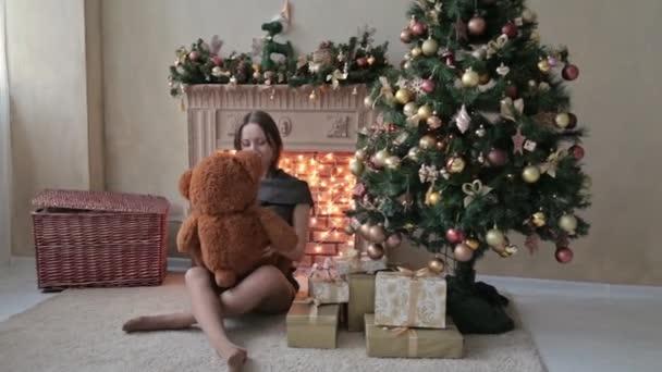 Fiatal nő ül a padlón, és ölelést, lök, touch egy nagy mackó, a karácsonyi díszek