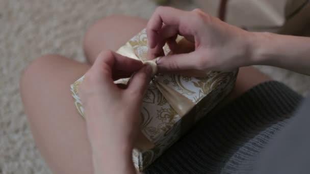 Mladá žena přivázat luk na vánoční krabičce