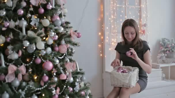Beautiful teenager girl sorting out christmas balls and decorating the Christmas tree