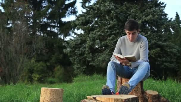 Mladý muž sedí v parku a čtení knihy
