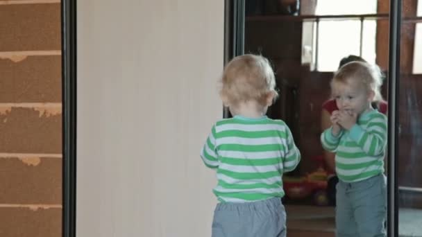 Little child have fun, play with ball near mirror