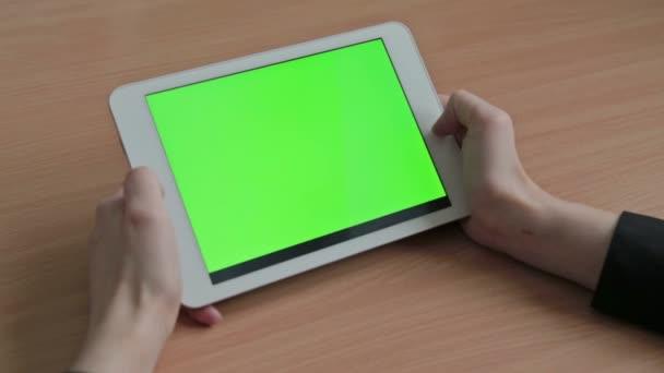 Donna che guarda il video su schermo del tablet, verde