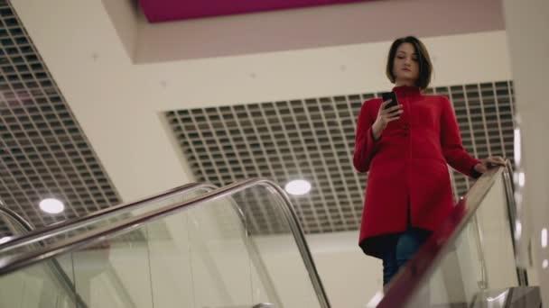 Frau tippt auf Smartphone-Gerät, während sie auf Rolltreppe fährt