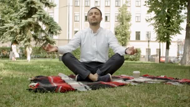 Man is meditating on green grass in the park with face raised up to sky and eyes closed on sunny summer day. Concept of meditation, dreaming, wellbeing and healthy lifestyle