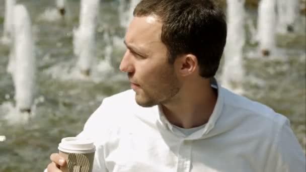 Mladý pohledný muž s šálkem kávy venku