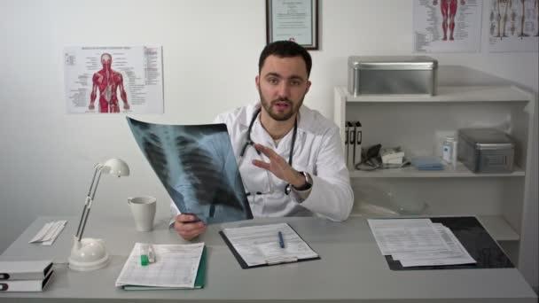 Doktor medicíny přátelské mluvící fotoaparát drží x-ray