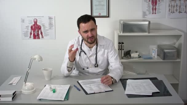 Terribile inquietante cause medico che parla alla telecamera con un sacco di gesti