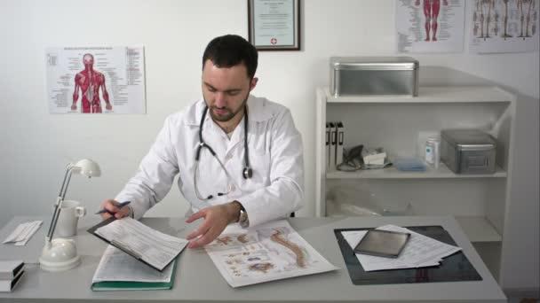 Fisioterapista nella sua pratica, il poster di colonna vertebrale sulla sua scrivania