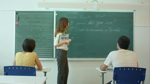 Fiatal tanár közelében Palatábla beszélt az osztály iskolai tanteremben