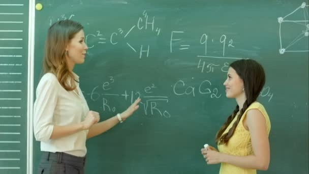 hezká mladá žena vysokoškolský student psaní na tabuli tabule při výuce chemie