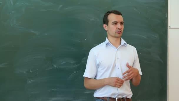 Fiatal tanár vagy diák mondani valamit a tábla közelében, és a gesticulate