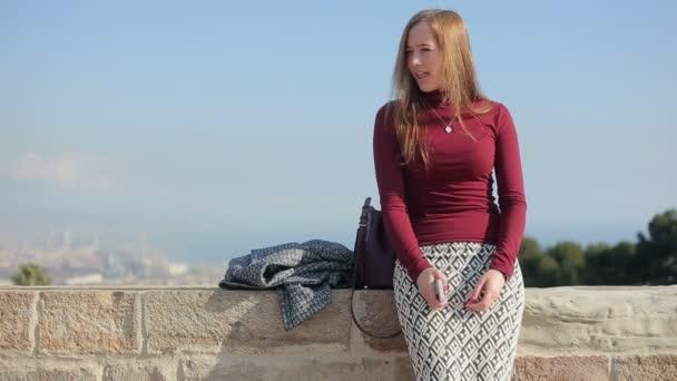 Hipster-Mädchen sitzt auf der Grenzmauer und singt