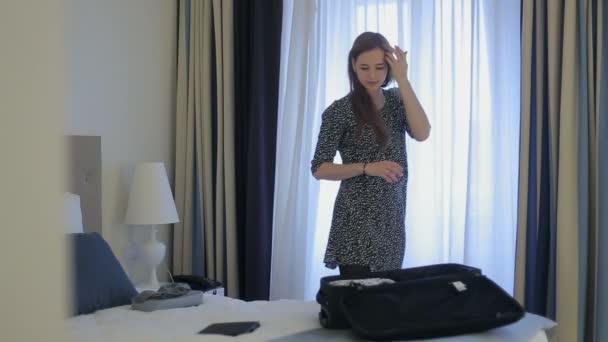 Žena kontrolu počasí venku a balit kufr, v hotelu