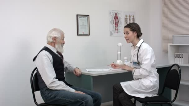 Doctor talking to her male senior patient and writing something.