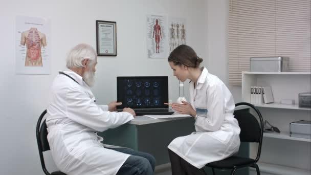 Orvosok a laptop számítógép megbeszélése betegek vizsgál.