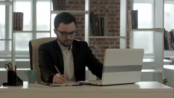 mladý muž s legrační brýlemi pracovat na svém notebooku, s čerstvý šálek kávy, pěkné a brzy ráno, váhavě z cesty a dobře naladěn v den