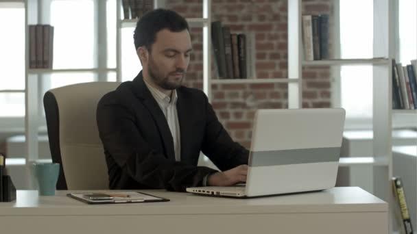 šťastný obchodní muž dokončil svou práci v kanceláři s notebookem