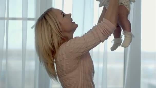 šťastná rodina. matka hází nahoru a líbání baby