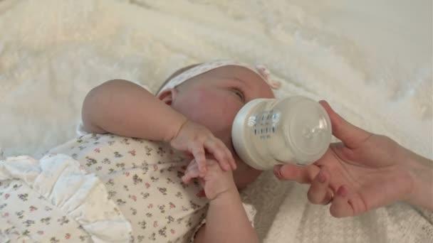 Little baby drinking milk from bottle.