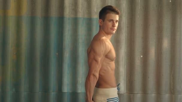 kulturista sportovní svalové silák, sportovní chlap ukazuje své mužské svaly, stojící bac