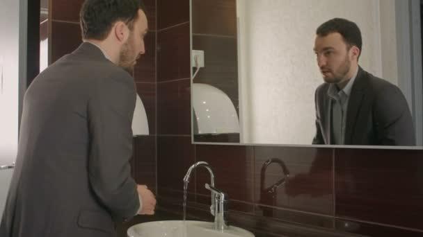 üzletember mosás arcát a fürdőszobában