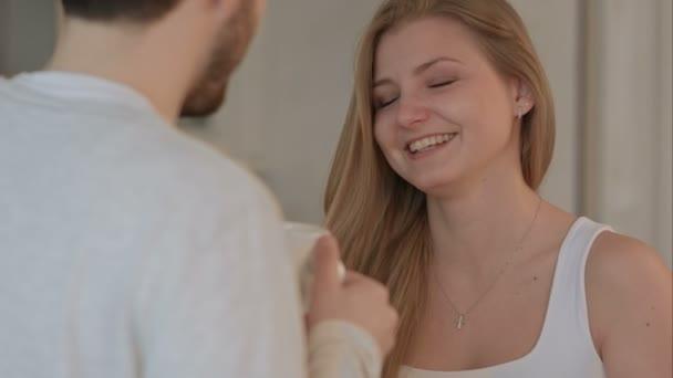 mladý muž dává dobré ráno polibek se svou ženou v kuchyni