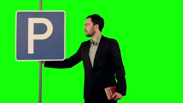 Man reading a book with parking sign on a Green Screen