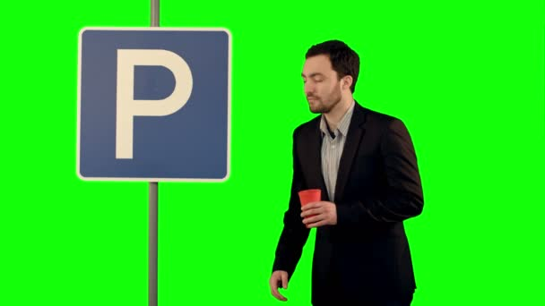 Man with cup of tea near parking sign on a Green Screen