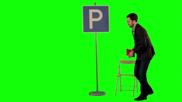 Businessman reading a book near parking sign on a Green Screen