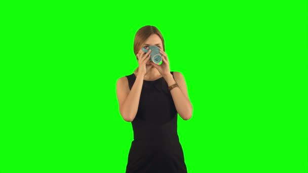 Young beautiful woman holding cup of tea or coffee  on a Green Screen