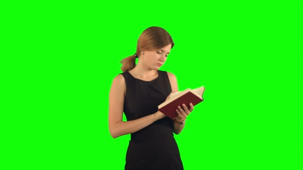 Young girl with book on laptop on a Green Screen, Chroma Key