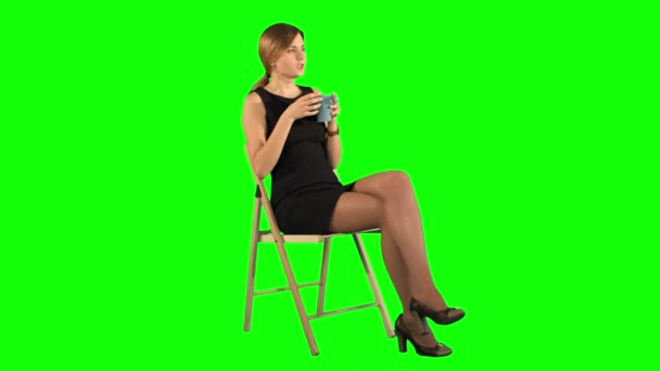 A young attractive woman with a cup of coffee or tea on laptop on a Green Screen, Chroma Key