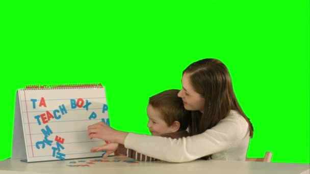 Mother and son make word Mama on the desk on a Green Screen