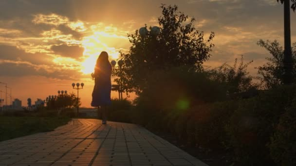 Dívka odchází a turnes zpátky při západu slunce.