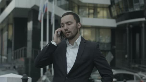 Orosz üzletember hívást telefonon, és magyarázza valamit az üzleti partnerek, az irodán kívül állva