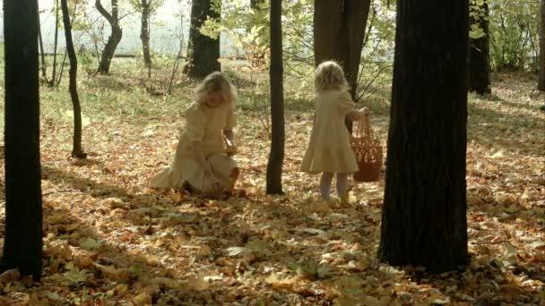 Šťastné matky s žlutým javor letáky objetí své dcery v podzimním lese
